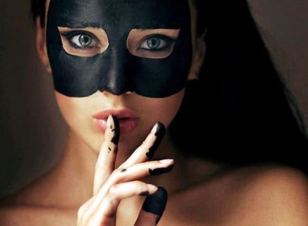 Черная маска из глины на лице
